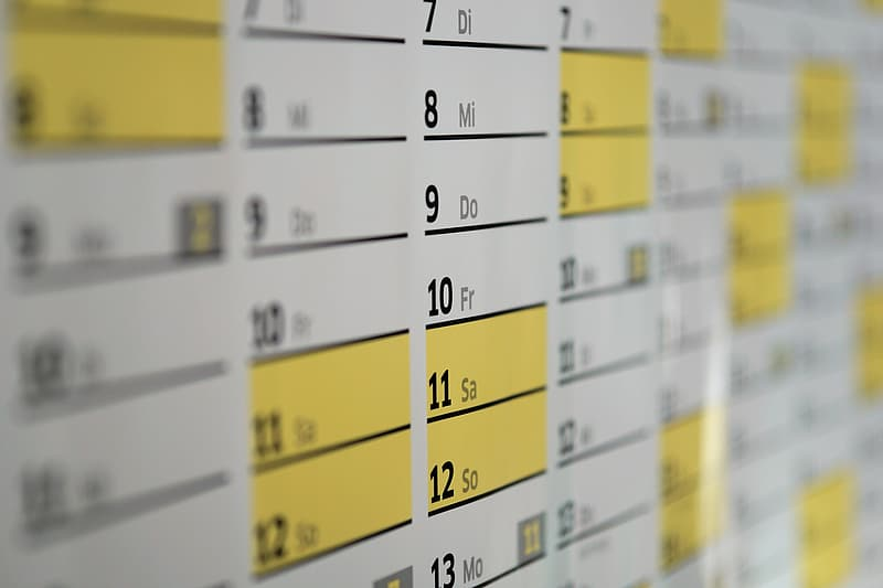 Closeup photo of white, yellow, and black calendar