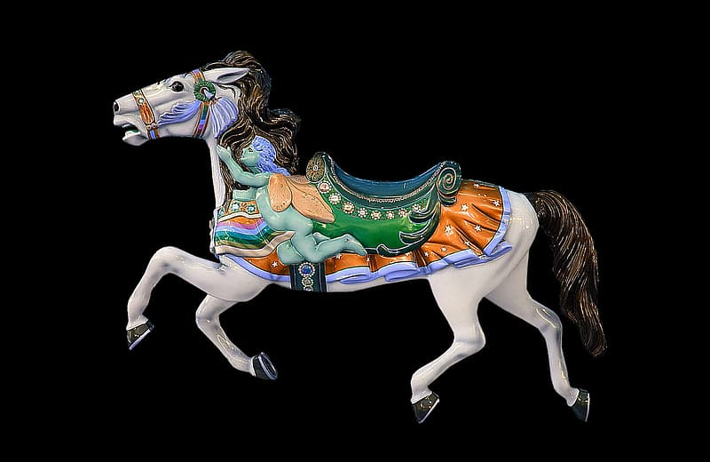 White and brown horse carousel against black background