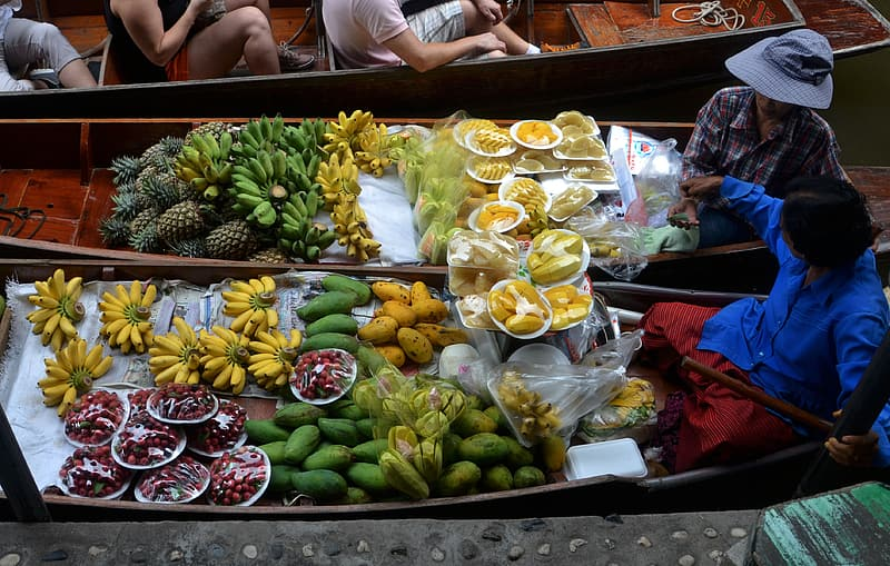 Assorted fruits on boats at daytime
