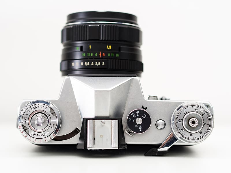 Gray and black DSLR camera placed on white surface