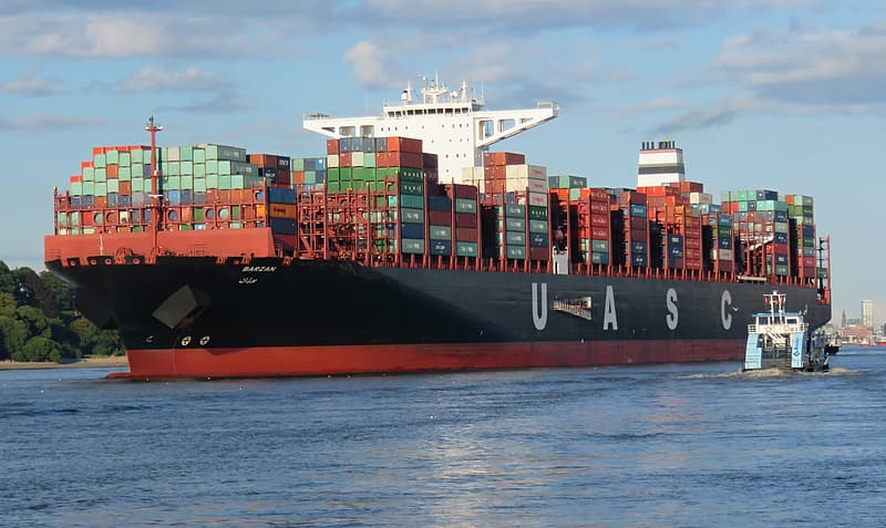 Red and black UASC cargo ship on body of water