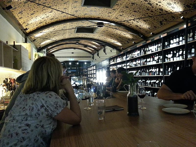 People sitting by the table inside bar with ceiling lights on