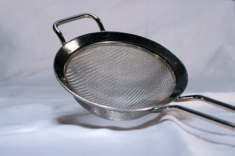 Stainless steel strainer on white textile