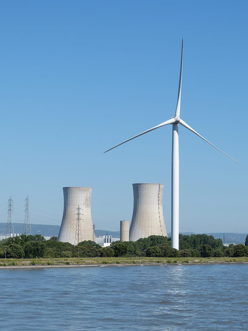 White wind turbines on green grass field near body of water during daytime