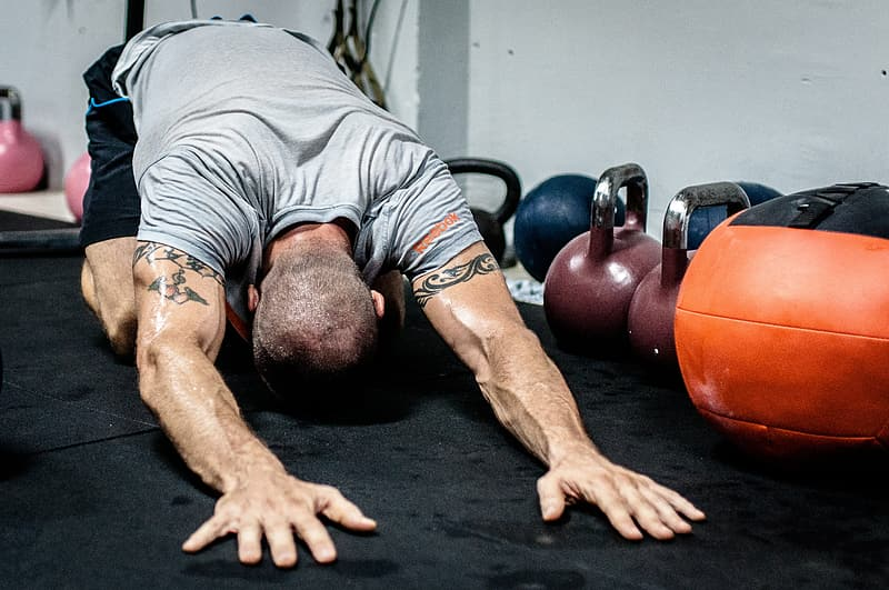 Body builder laying his hands on floor near kettle dumbbells