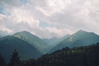 White clouds over green mountains