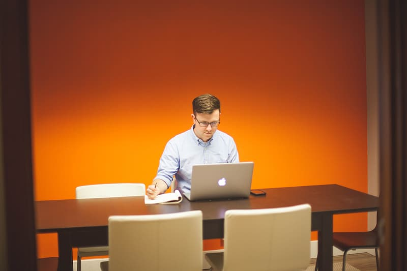 Man in blue dress shirt wearing eyeglasses sitting on chair while looking at the silver iMac and holding pen