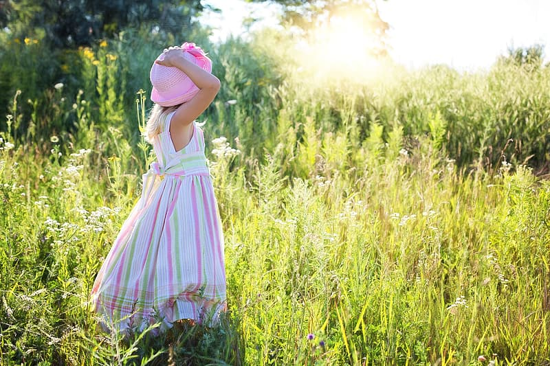 Girl standing on green grass field while holding her pink hat during daytime