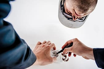 Person in blue sleeves repairing white bulb socket