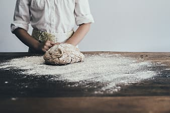Person wearing white dress shirt facing flour on table