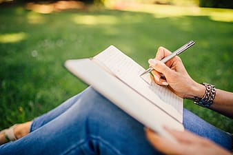 Person writing on notepad sitting on green grass in selective focus photography at daytime