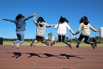 Four woman in jacket jumping altogether during daytime