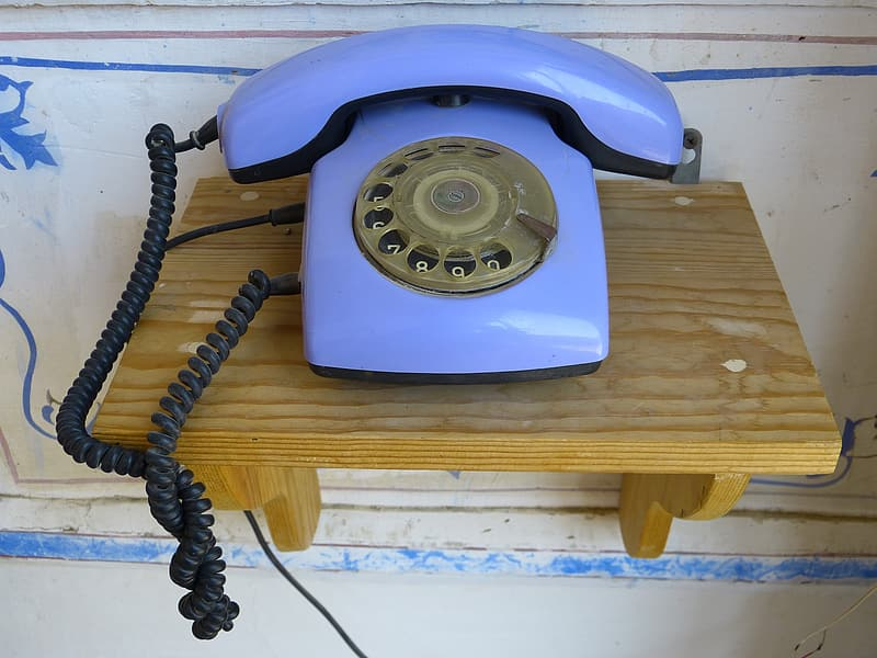 Blue rotary phone on brown wooden shelf