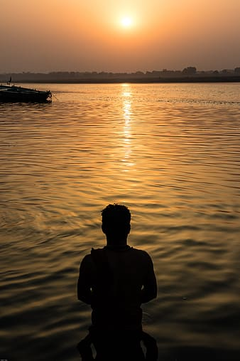 Silhouette of man standing on water during sunset