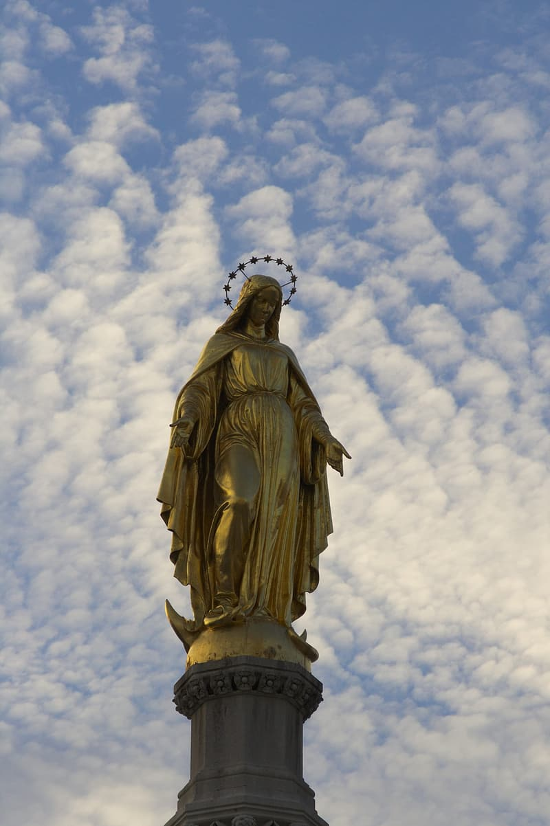 Gold statue under white clouds during daytime