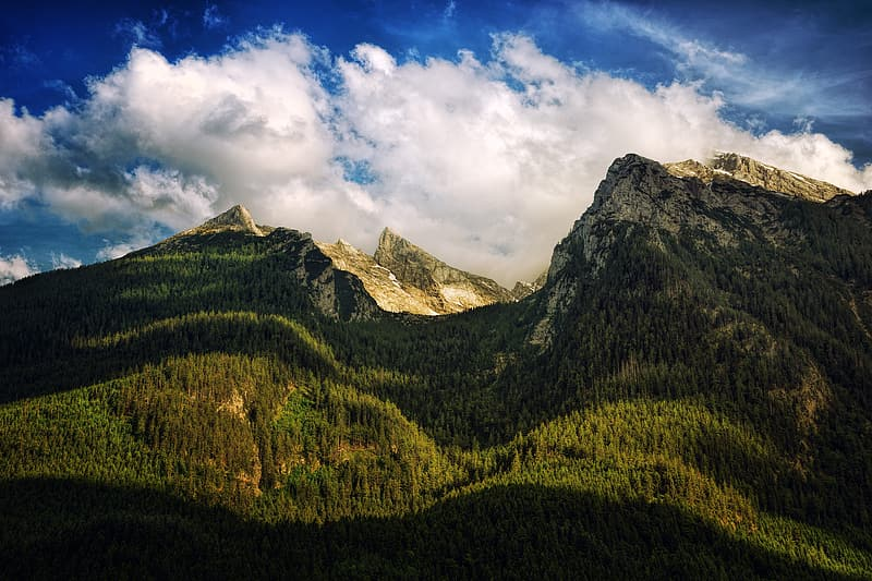Green trees and mountain under white clouds and blue sky during daytime