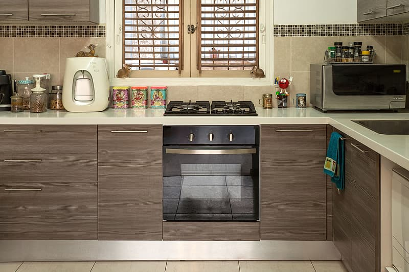 Brown wooden kitchen cabinet with built in gas range oven