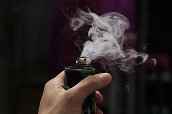 Person holding black lighter with white smoke