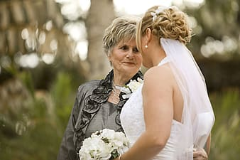 Woman wearing wedding dress beside woman wearing gray blazer