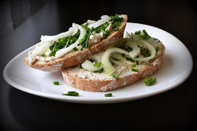 Bread with green vegetable on white ceramic plate