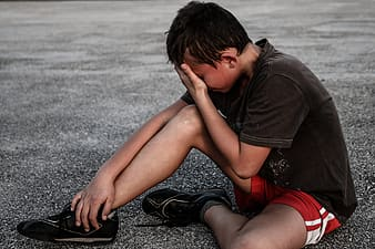 Boy in brown shirt and red gym shorts sitting on concrete floor