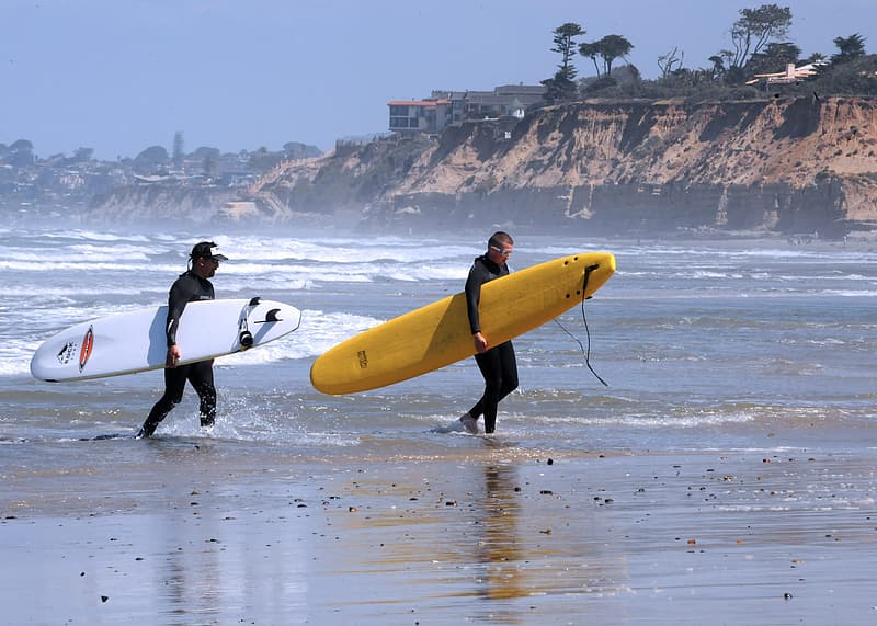 Man in black wet suit holding yellow surfboard on beach during daytime