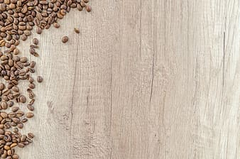 Roasted brown coffee beans scattered on brown wooden surface