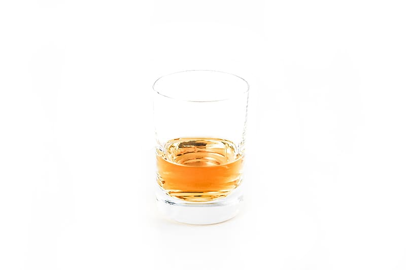 Clear shot glass with brown liquid