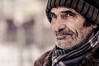 Selective focus photograph of man wearing black knit cap and black scarf