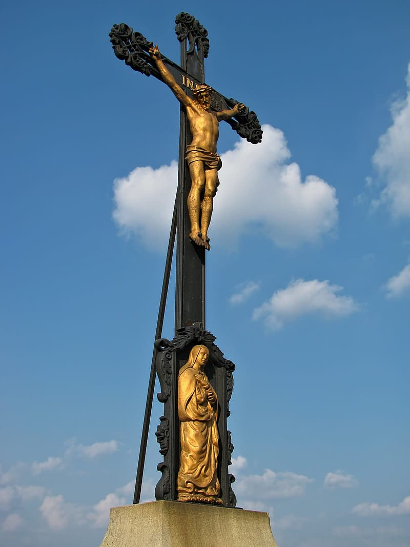 Gold statue of man holding cross under blue sky during daytime
