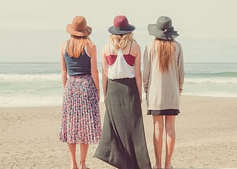 Three women standing at the beach looking at the ocean during day