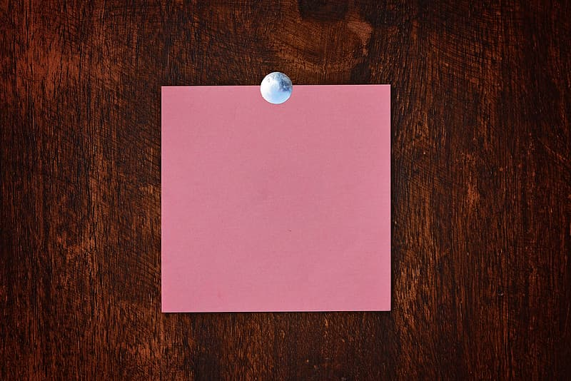 Pink paper on brown wooden table