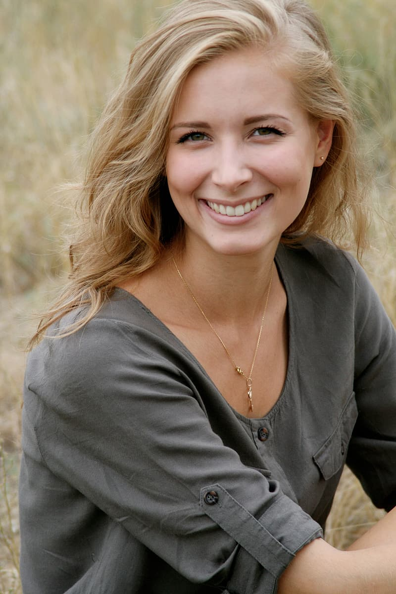 Shallow focus photography of blonde haired woman in gray long-sleeved blouse