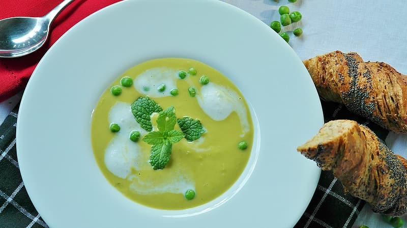 Yellow and green cream soup on white plate