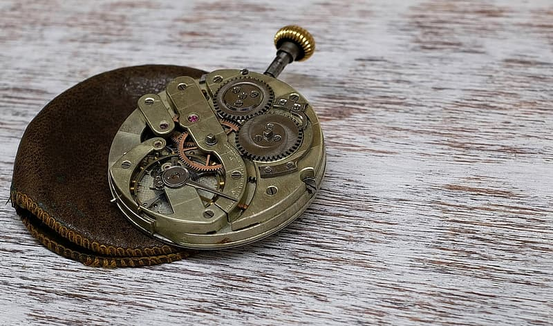 Photo of brass-colored skeleton pocket watch on leather case