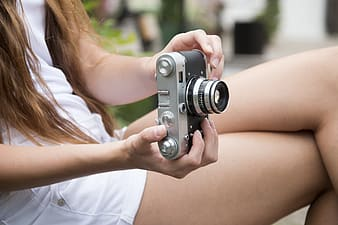 Woman wearing white top holding camera