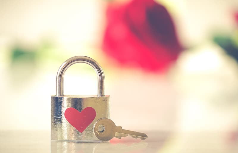 Red and silver padlock on white surface