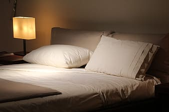 Empty bed with white comforter set beside turned on table lamp
