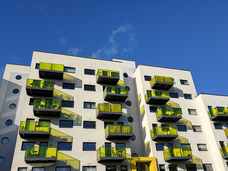 White painted building with yellow balcony under blue sky