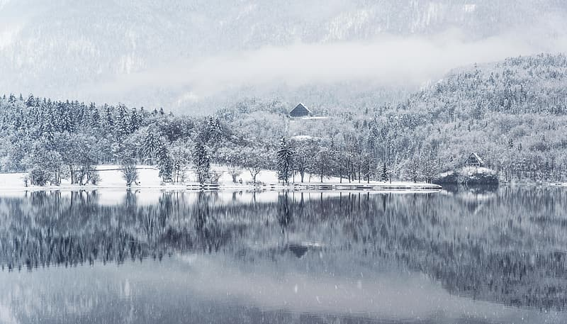 Body of water near snow covered mountain