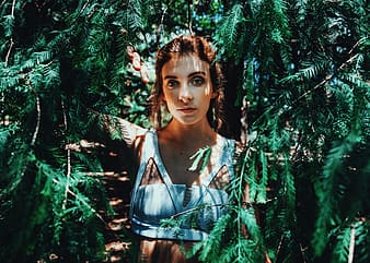 Woman wearing blue sleeveless crop top standing between green plants