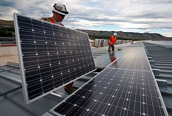 Two men in red reflector vests positioning some solar panels