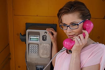 Woman holding pink telephone inside booth