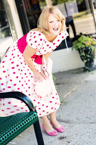 Selective focus photography of woman in white and pink polka-dotted dress