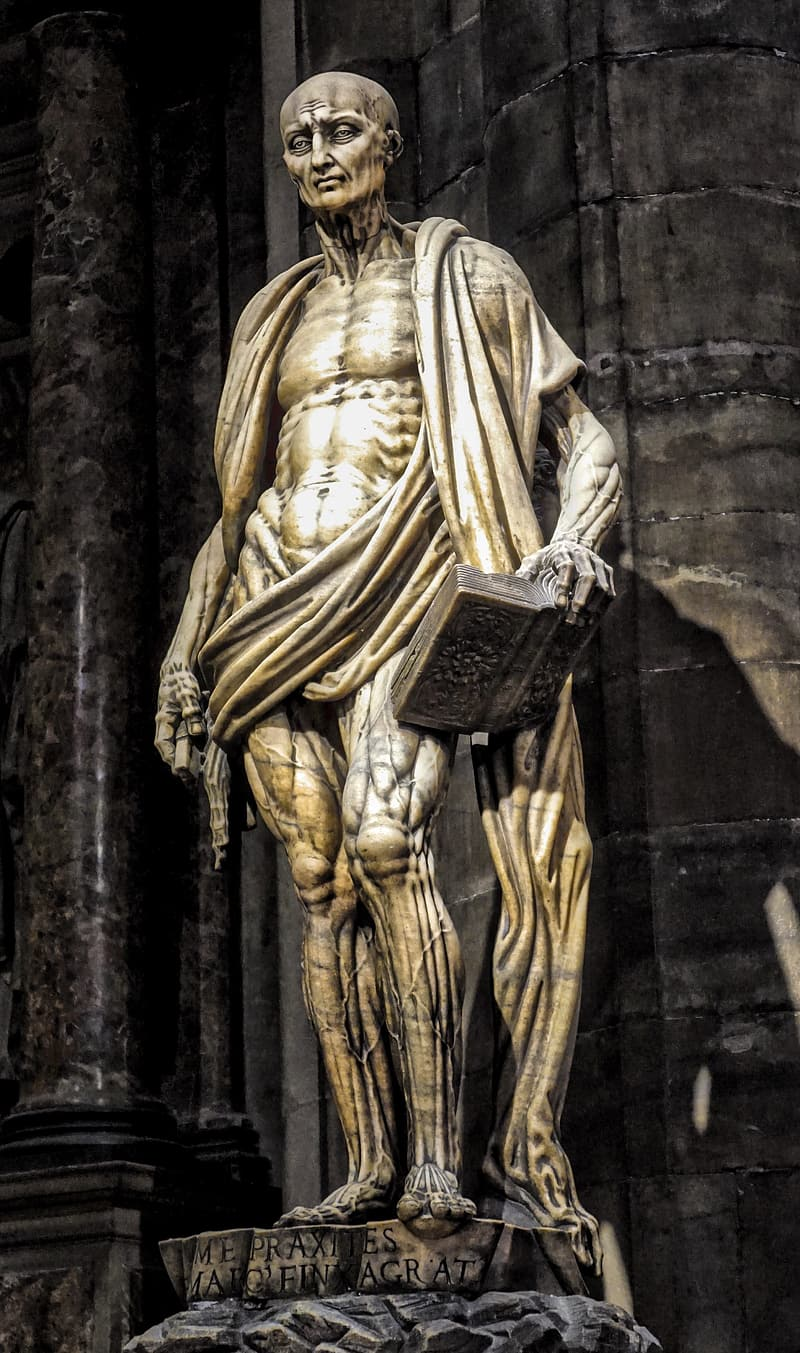 Gold statue of man holding book