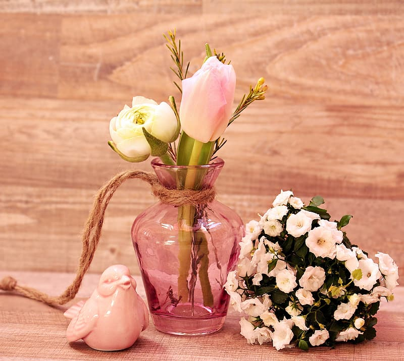 Pink and white petaled flower with pink tinted glass vase near white ceramic bird figurine