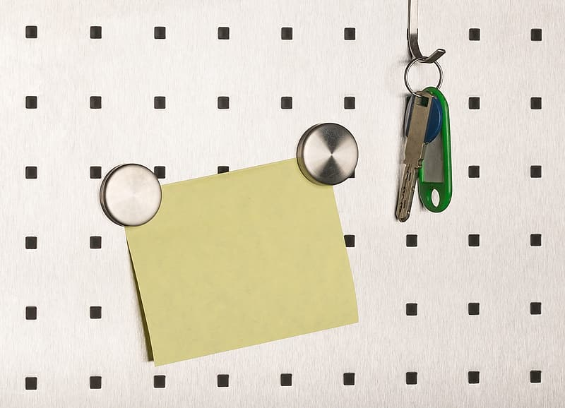 Silver and green magnifying glass beside yellow paper