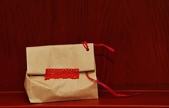 Beige paper bag on red surface