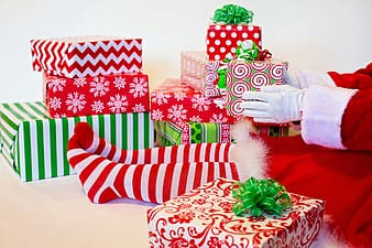 Person wearing red and white santa dress sitting down near gifts holding green and red present