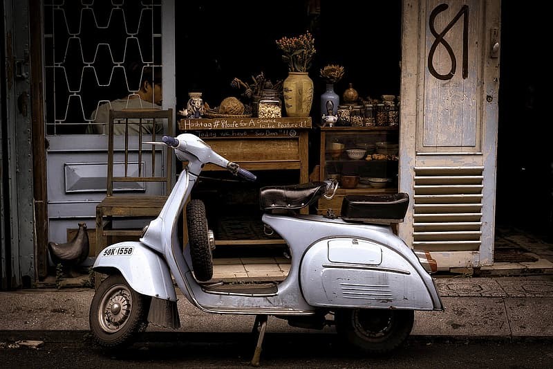 Gray motor scooter parked infront of store